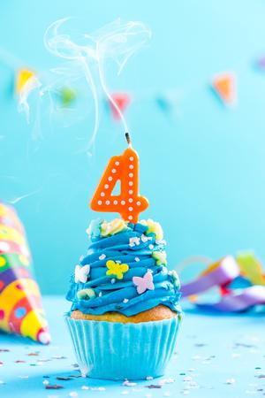 キャンドルを吹き飛ばし、振りかける4歳の誕生日カップケーキ。カードモックアップ。