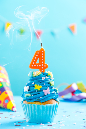 Fourth 4th birthday cupcake with candle blow up and sprinkles. Card mockup. Stock Photo