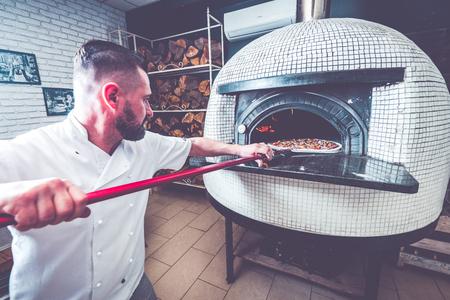 Bearded man chef preparing pizza at local business.