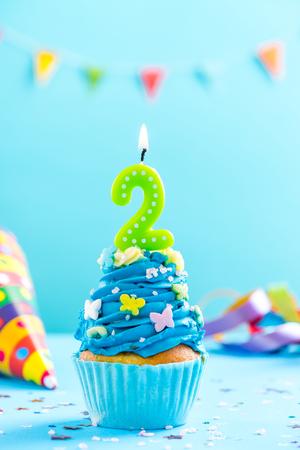 キャンドルと振りかける2番目の誕生日カップケーキ。カードモックアップ。 写真素材