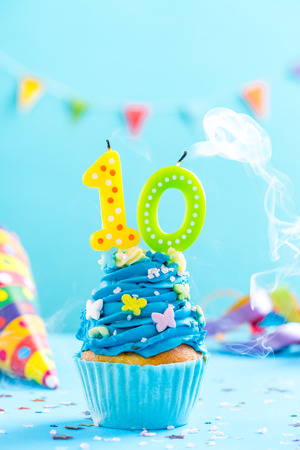 Tenth 10th birthday cupcake with candle blow up and sprinkles. Card mockup. Stock Photo