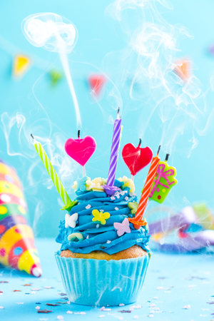 Colorful decorated cupcake with candles blow up. Birthday card mockup. Stock Photo
