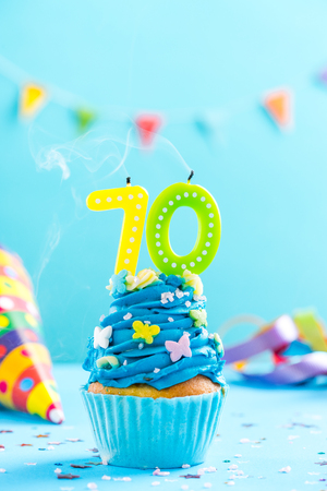 Seventieth 70th birthday cupcake with candle blow up and sprinkles. Card mockup. 스톡 콘텐츠
