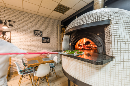 Beau pizzaiolo homme pizza au four à bois dans une pizzeria locale