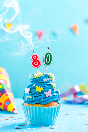 Eightieth 80th birthday cupcake with candle blow up and sprinkles. Card mockup. Imagens