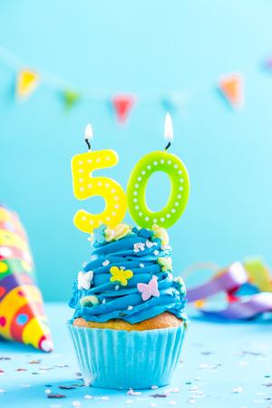 50歳の誕生日カップケーキとキャンドルと振りかける。カードモックアップ。