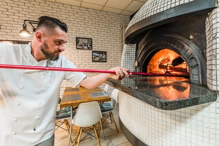 잘 생긴 pizzaiolo 남자 지역 피자 가게에서 woodfired 오븐에서 피자 굽기