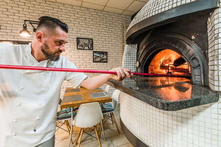 Handsome pizzaiolo man baking pizza in woodfired oven in local pizzeria