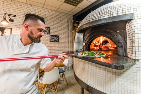Bearded pizzaiolo man baking pizza in woodfired oven in local pizzeria Stockfoto