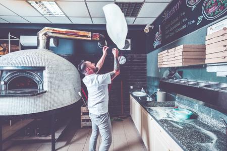 Bearded pizzaiolo chef lunching dough into air. Foto de archivo