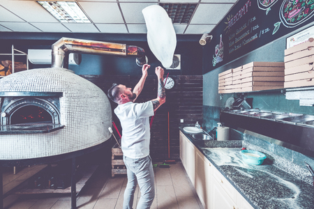 Bearded pizzaiolo chef lunching dough into air. Archivio Fotografico