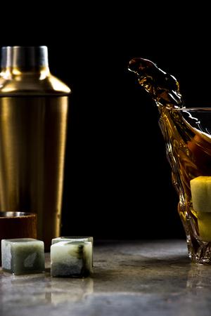 Dynamic photo of whiskey splash from glass on dark background Stock Photo