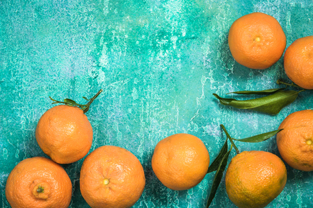 Fresh clementines over concrete slate background, food border