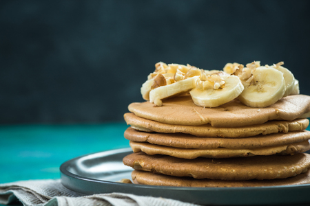 Healthy brunch, pancakes topped with banana and nuts