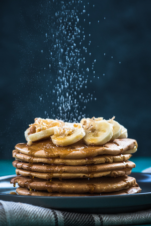 パンケーキの上を飛ぶ砂糖を振りかける 写真素材