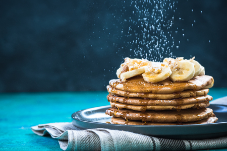 Sugar sprinkles flying over pancakes pile. Copy space. Фото со стока