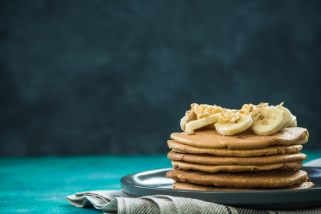 Healthy brunch, pancakes topped with banana and nuts Stok Fotoğraf - 93148835