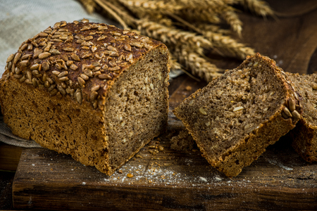 Wholegrain bread with seeds sliced on board. Imagens - 93698126
