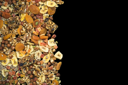 Dried fruits and nuts isolated on black, border background