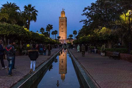 Marrakech,Morocco - January 24th 2018: Moroccan people walking in gardens by Koutoubia Mosque in Marrakesh,Morocco.