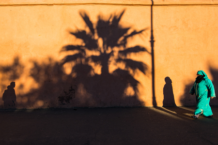 Marrakech,Morocco - January 2018:Muslim woman past by wall full of shadows in traditional clothes. Editorial
