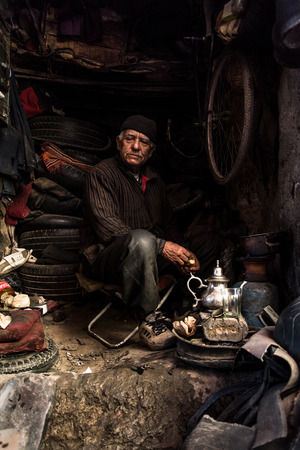 Marrakech,Morocco - January 2018: Local man in street obscure workshop havin tea break in poor conditions in marrakesh.