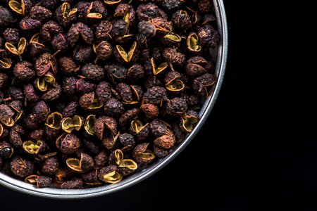 Pot with Timut Nepalese pepper on dark background with copy space Stock Photo