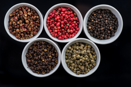 Five different pepper seeds in pots, oriental spices mix 스톡 콘텐츠