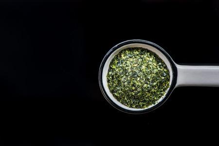 Dried aonori seaweed flakes on spoon. Stock fotó