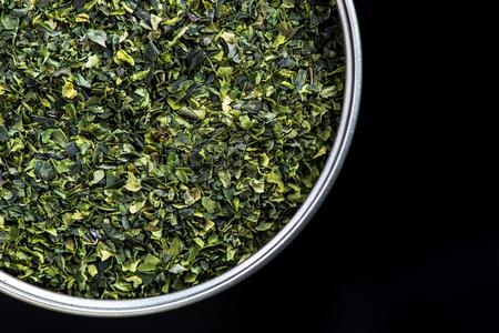 Aonori seaweed flakes in pot, copy space.