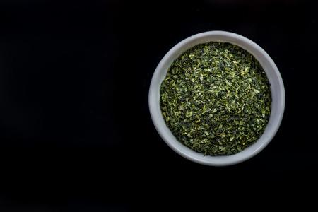 Dried aonori seaweed flakes in pot on dark. Stock fotó
