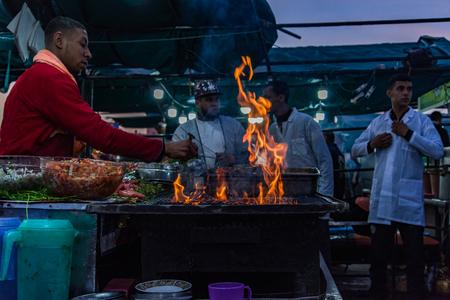 マラケシュ、モロッコ - 1月 2018:モロッコの有名なジャマエルフナ市場でオープン火災グリルの上にシェフ料理