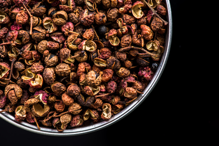 Sichuan pepper on pot on dark background with copy space. Stock Photo