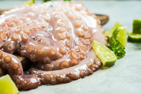 Whole fresh octopus on cutting board.
