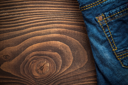 Blue denim jeans on wooden background with copy space