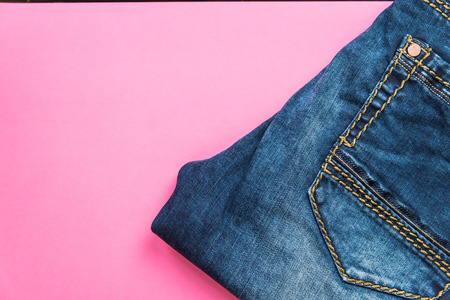 Blue jeans on pink pastel background.