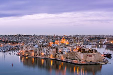 Illuminated skyline of Senglea at twiligh sunset,Malta. Фото со стока