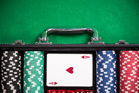 Suitcase with poker chips on poker table.