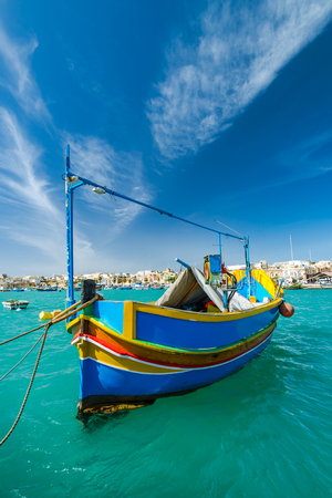 Beautiful painted fishing boat on turquoise water in Marsaxlokk,Malta. Stok Fotoğraf