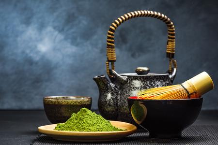 Green matcha tea,tea pot and bowl. Copy space on dark background.