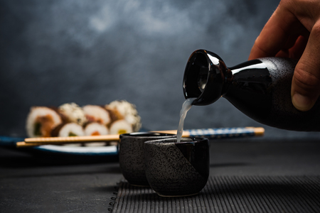 Man pouring sake into sipping bowl.