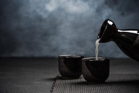 Pouring sake into sipping ceramic bowl.