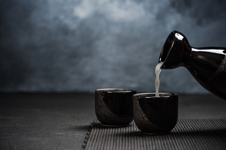 Pouring sake into sipping ceramic bowl.