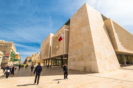 VALLETTA, MALTA - MARCH , 2018: People walking past Valletta Parliament building at sunny day.