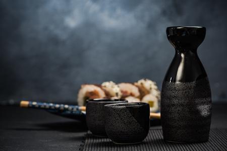 Drinking traditional sake and eating sushi. Stock Photo