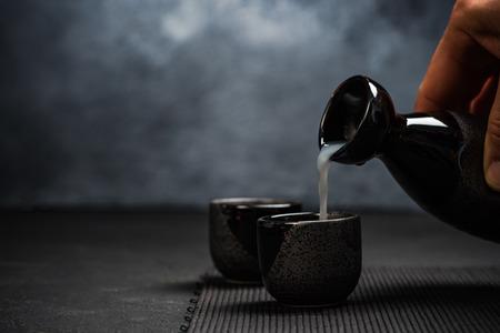 すすりボウルに酒を注ぐ男。