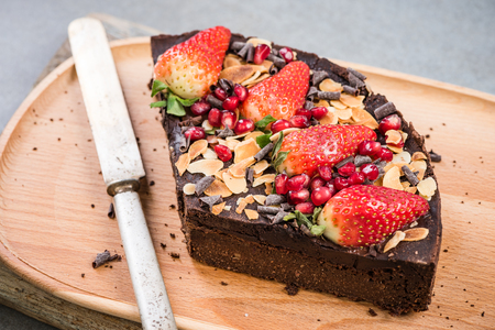 Slice of healthy brownie with strawberry and pomegranate seed.