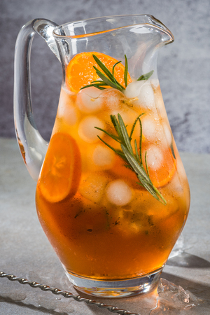 Ice cold tea with rosemary in pitcher.