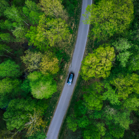 Car driving on road in forest,aerial view.