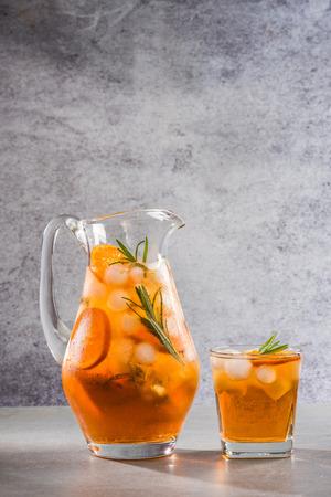 Iced peach tea in jug, summer refreshing drink.